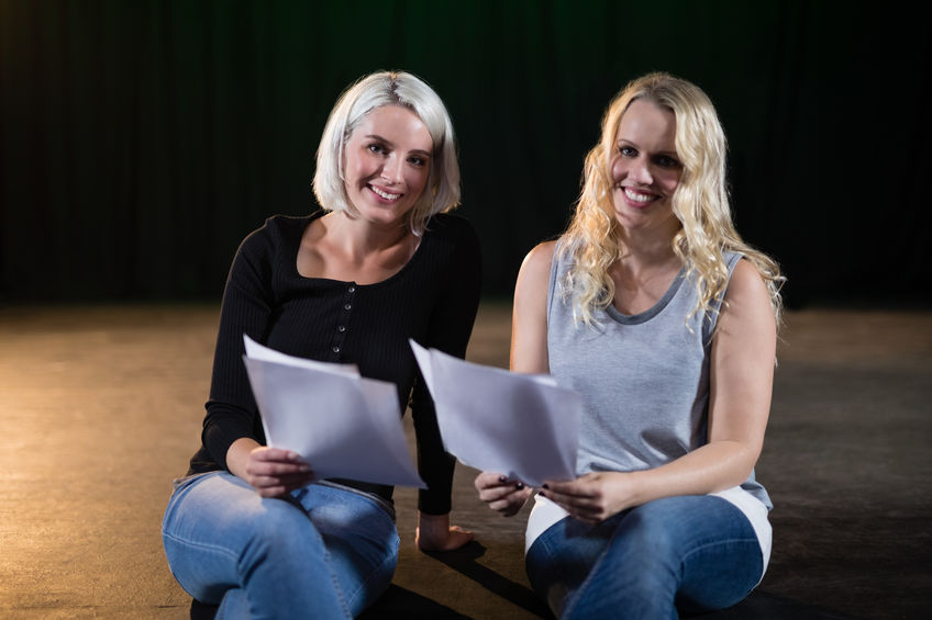 Photo - Two actresses read a script sitting on a stage